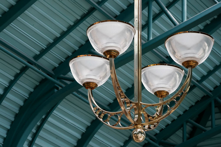 Low angle view of lighting equipment hanging from ceiling