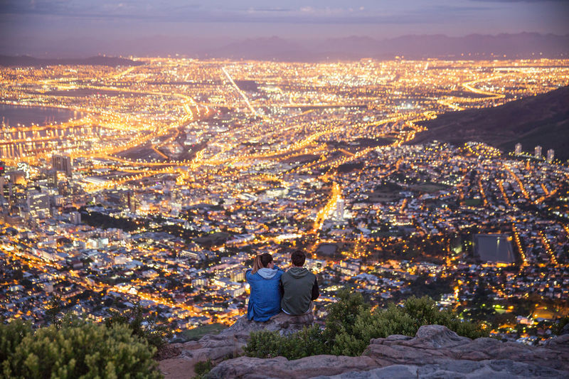 Rear view of man and woman sitting on mountains against illuminated city at dusk