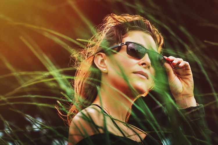 Girl in sunglasses behind tall grass Adult Beautiful Woman Fashion Front View Glasses Headshot Leisure Activity Lifestyles Nature One Person Outdoors Plant Portrait Real People Sunglasses Women Young Adult Young Women