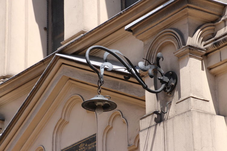 Low angle view of electric lamp hanging on building