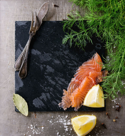 Sliced salted salmon fillet, fresh dill, sliced lemon and sea salt with empty black stone slate board and vintage cutlery over textured iron background. Flat lay. Space for text. Square image Salmon Fillet Fresh Cooking Food Fish Healthy Raw Seafood Diet Lemon Background Pepper Delicious Dill Herbs Spices Slate Gourmet Tasty Salt Meal Stone Textured  Empty Space Text Steak Dinner Restaurant Concept Black Vegetables Board Aromatic Vegetable Ingredient Portion Flat Top View Above Overhead Metal Iron Cutlery Fork Vintage Square