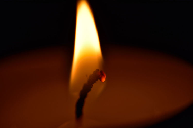Close-up of lit tea light candle in dark room