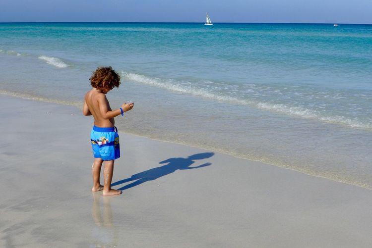 Child Playing With His Shadow At Beach