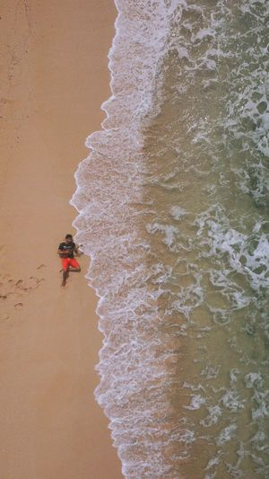 High angle view of man lying on shore at beach