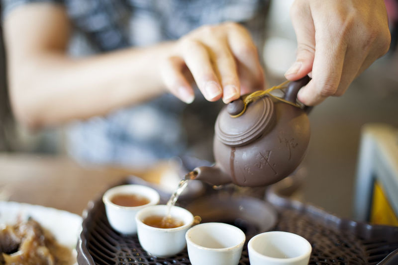 A young man is preparing some tea to start his day. Asian  Background Beverage Blue Bokeh Brown China Chinese Culture Chinese Tea Chinese Tea Cup Chinese Tea Pot Close-up Culture Day Drink Drinking East Hands Healthy Indoors  Lifestyle Pouring Relaxation Tea Tea - Hot Drink