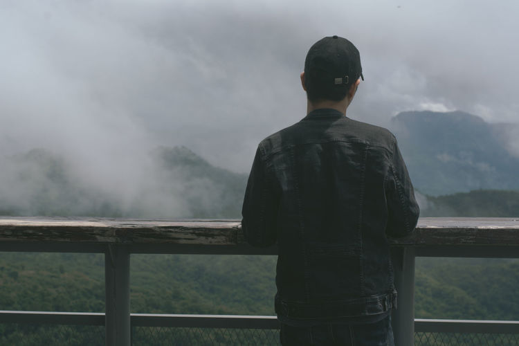 Rear view of man looking at view of mountains against sky