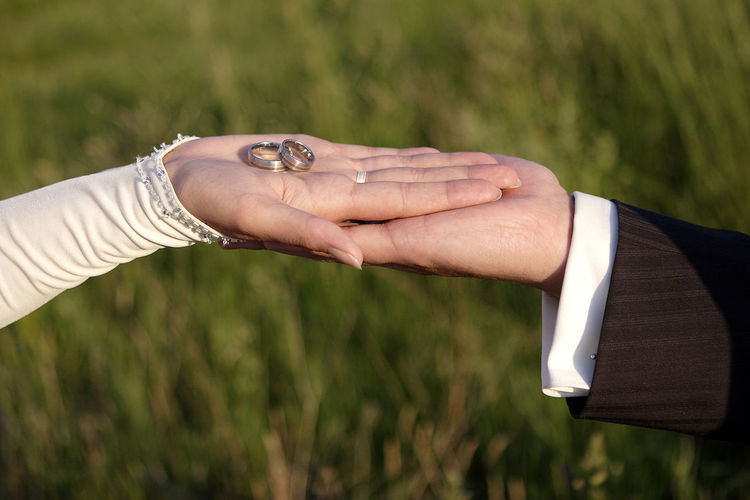 Close-Up Of Couple Holding Wedding Rings