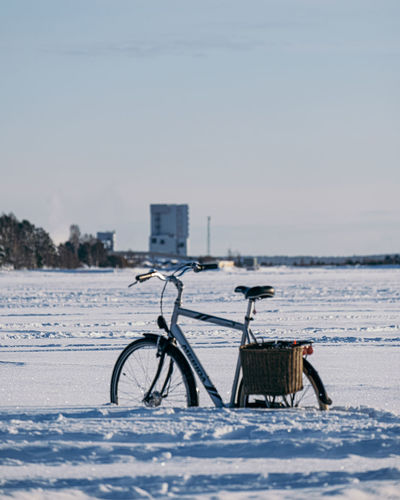 Bicycle on snow covered land against sky