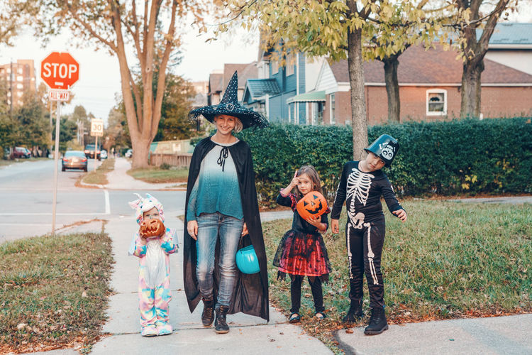Mother and kids wearing costume standing outdoors