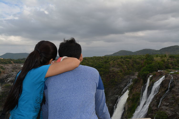 Rear view of young couple looking at waterfall at mountain against cloudy sky