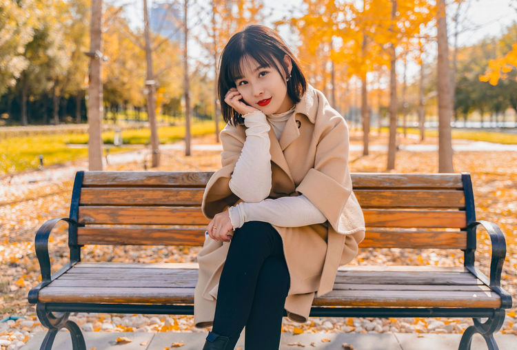Portrait of beautiful woman sitting on bench in park