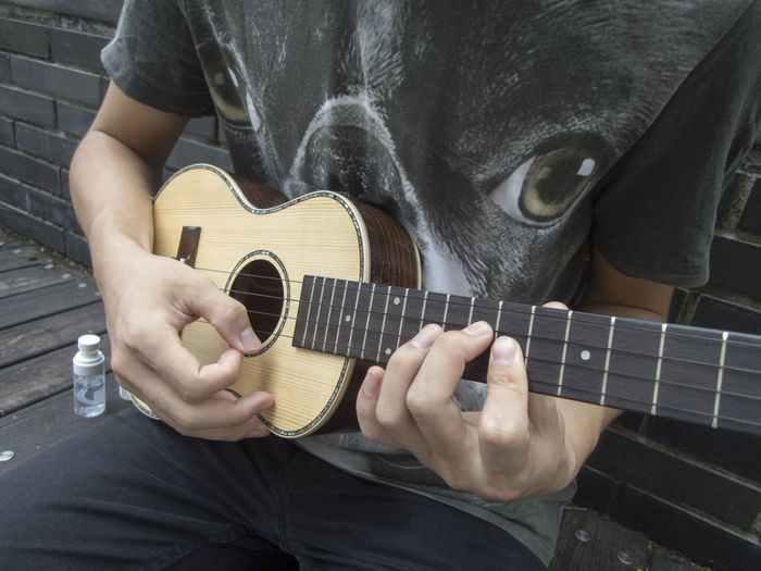 Midsection of man playing ukulele