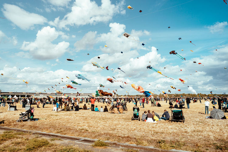 Kites flying over people on field against cloudy sky