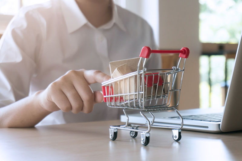 Midsection of man touching miniature shopping cart by laptop on table