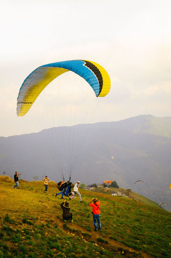 Ready to Fly High Adventure Exhilaration Extreme Sports Flying Freedom Go Higher Group Of People Joy Leisure Activity Lifestyles Men Mid-air Mountain Mountain Range Nature Outdoors Parachute Paragliding People Real People Sky Sport Unrecognizable Person