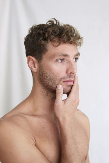 Portrait of shirtless man looking away against white background