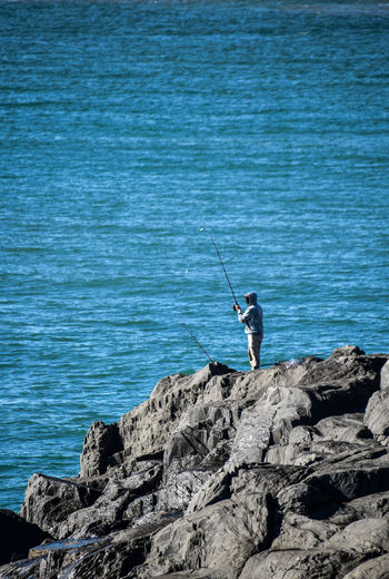Man fishing on rock by sea