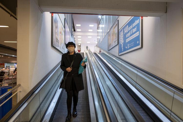 Woman wearing mask standing on escalator