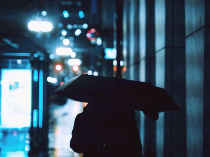 Silhouette Person Holding Umbrella On Street During Rainy Season At Night