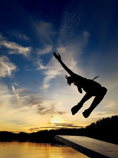 Silhouette man jumping against sky at sunset