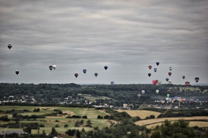 Hot Air Balloons Flying In The Bristol Balloon Fiesta Against Cloudy Sky
