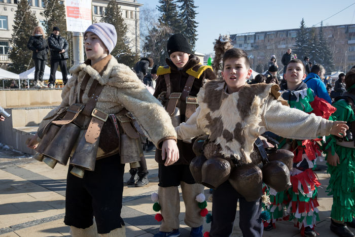 PERNIK, BULGARIA - JANUARY 26, 2018: Boys in traditional fur costumes and several big brass ritual bells dance, jump, shout and make strong noise at the International Festival of Masquerade Games Dance Kukeri Teenagers  Adult Bulgarian City Cold Temperature Dancers Day Friendship Full Length Looking At Camera Outdoors People Portrait Standing Surva Teenager Warm Clothing Winter Young Adult