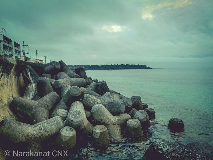 Stack of rocks on beach against sky