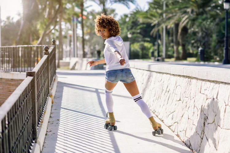 Young black woman on roller skates riding near the beach. Girl with afro hairstyle rollerblading on sunny promenade with sun backlight. Afro Black Woman Fun Hairstyles Happy Rear View Sunlight Afrohair Beautiful Woman Curly Hair Hairstyle Leisure Activity Roller Skating Rollerblading Rollerskates Rollerskating Skate Skater Sport Sports