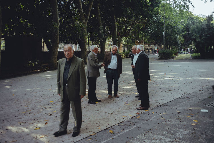 Senior Men Wearing Full Suits While Standing At Park