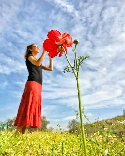 Low angle view of woman standing by red flowering plant against sky