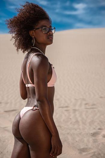 Young woman in bikini standing on beach