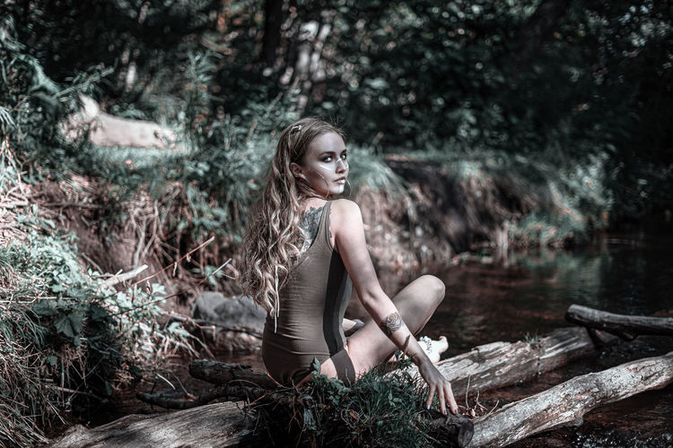 Young woman sitting on tree in forest