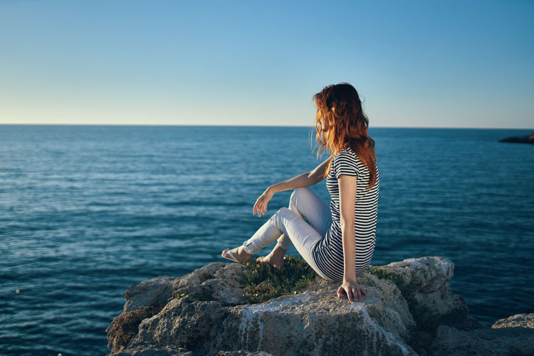 Woman sitting on rock looking at sea against clear sky