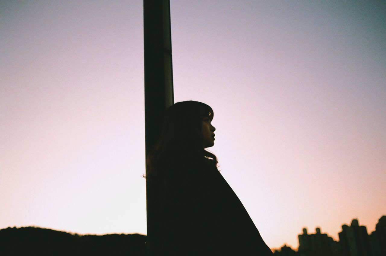 Side view of thoughtful woman leaning on pole against clear sky during sunset