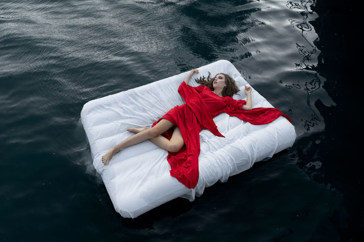 High angle view of young woman relaxing on bed floating in lake