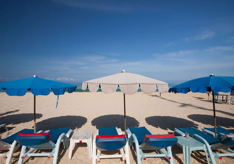 Chairs and parasols on beach against blue sky