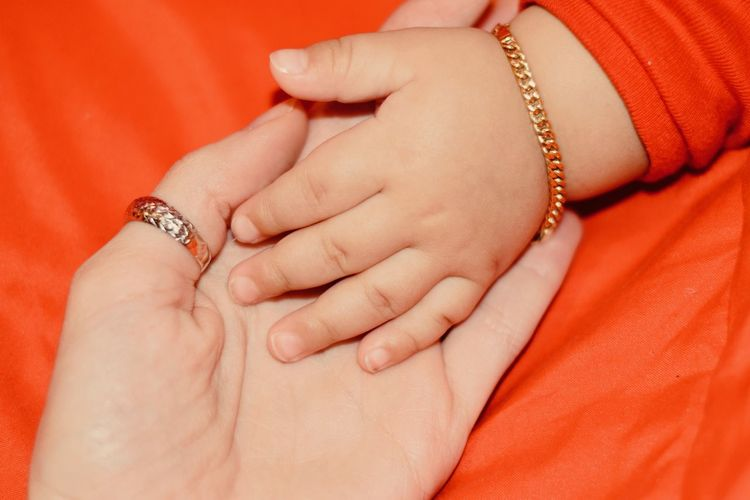 Cropped Hand Of Mother Holding Baby Girl