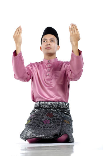 Portrait of young and handsome asian man with traditional clothing during hari raya over white background White Background Studio Shot One Person Front View Cut Out Indoors  Young Adult Human Arm Standing Women Casual Clothing Young Women Adult Portrait Three Quarter Length Females Clothing Looking Arms Raised