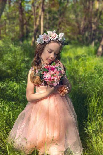 Girl holding flowers on field