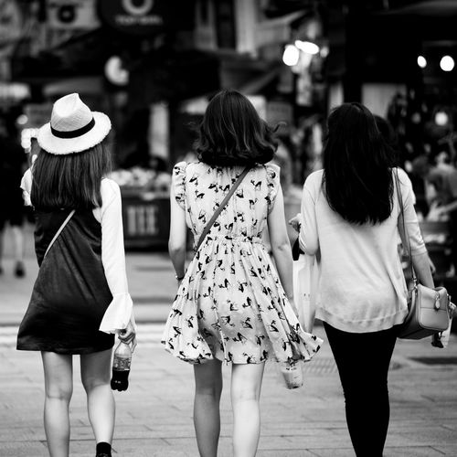 Rear view of women walking on street