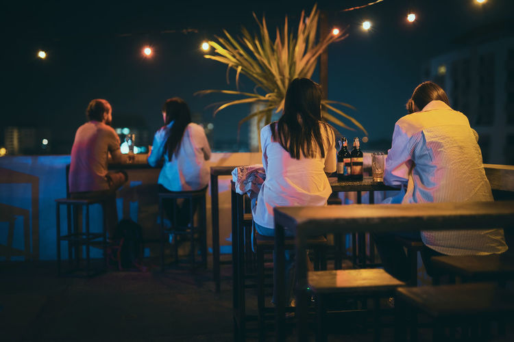 Rear view of people sitting in restaurant at night