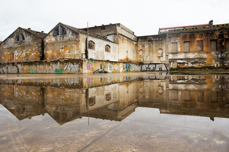 Architecture Building Exterior Built Structure Day Dilapidated Building Forecourt Grafitti Lostplaces No People Old Buildings Old Industry Old Warehouse Outdoors Reflection Reflections In The Water Sky Uninhabitable Urban Vacant Building Water