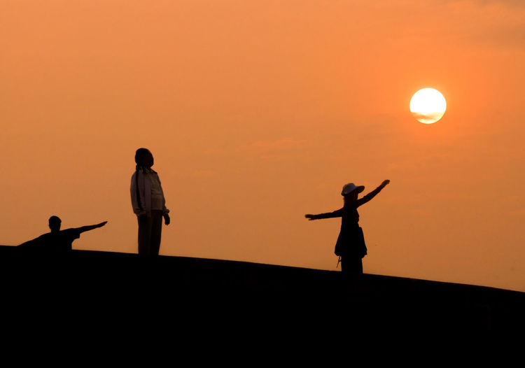 People standing by scarecrow against orange sky