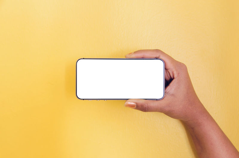 Midsection of person holding smart phone against yellow wall