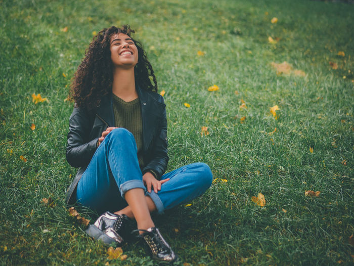 Cheerful Young Woman Sitting On Grass