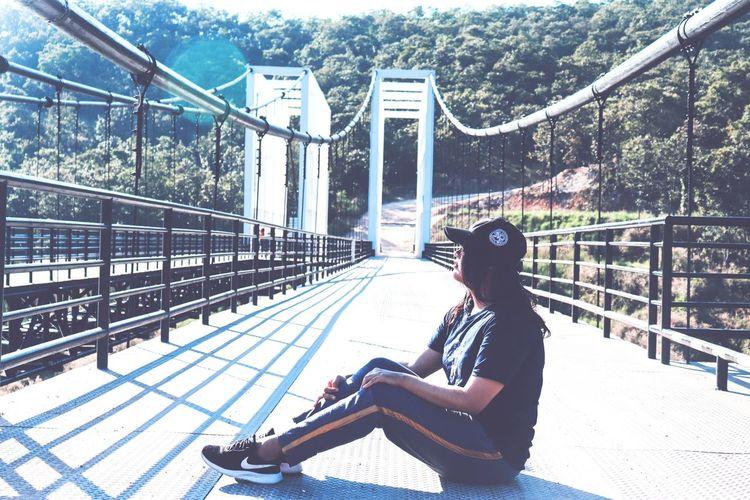 Side view of man sitting on bridge