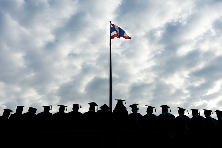 The graduates stand in-line to take group photo. Achievement Celebration Congratulations Graduation Happy Meeting Students Thailand Ceremony Cloud - Sky College Commencement Day Finish Flag Graduates Group Of People Group Photo Low Angle View Nature Outdoors School Silhouette Sky University