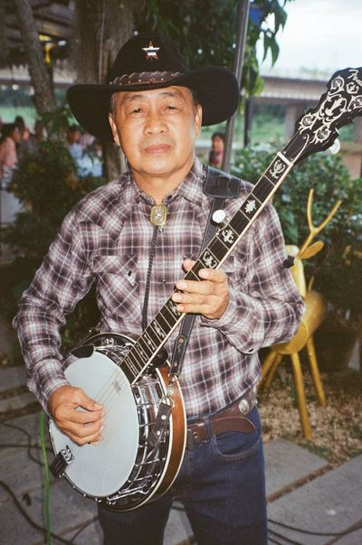 if you play it, they will come -- chiang rai thailand november 2016 35mm Film Analogue Photography Asian Cowboy Banjo Banjo Player Bluegrass Festival Chiang Rai, Thailand Country Music Cowboy Hat Film Photography Filmisnotdead Musician One Man Only Plaid Shirt  Plucking An Instrument Standing Street Photography Street Portrait TakeoverMusic Thailand_allshots