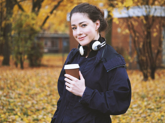 Smiling One Person Young Adult Autumn Looking At Camera Lifestyles Portrait Young Women Outdoors Fall Colors Season  Girl Real People Brunette Nature Park Technology Holding Wireless Technology Headphones Coffee Cup Cold Weather Hot Drink Coffee Cup Coffee To Go Disposable Cup