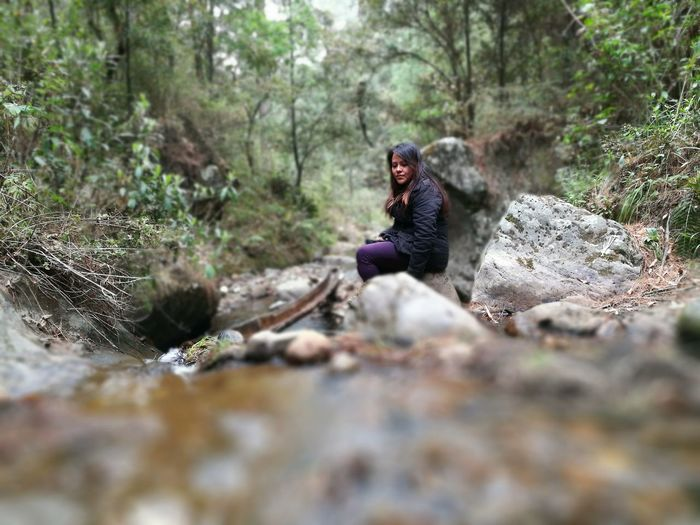 Thoughtful young woman sitting on rock in forest